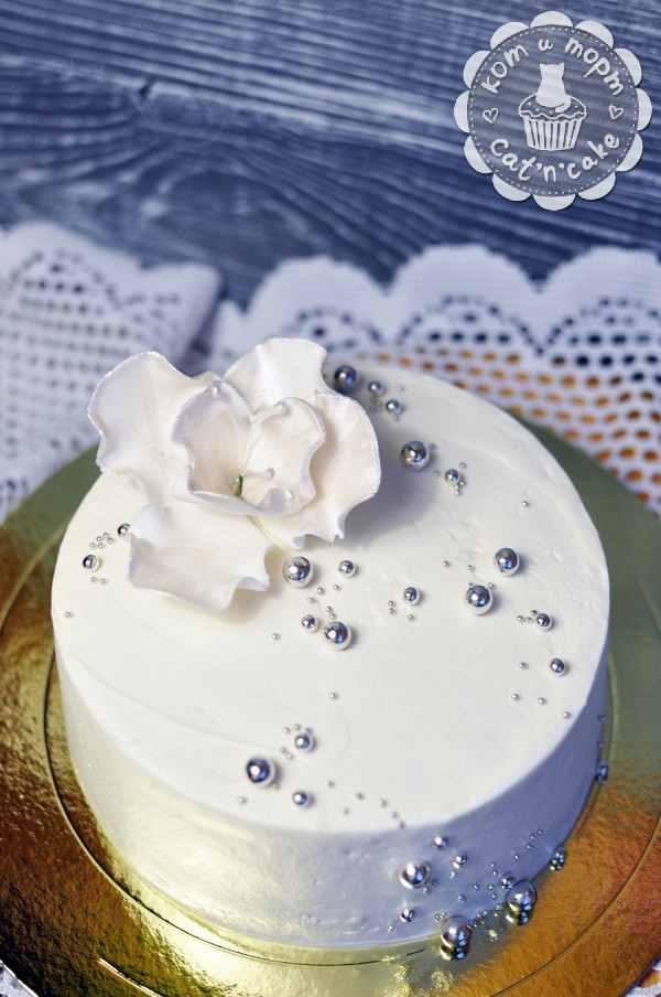 Белый торт с цветком и серебряными бусинками