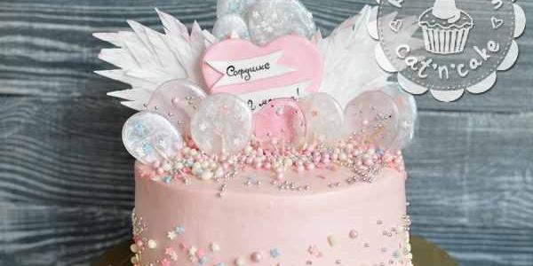 Розовый торт с леденцами и перьями